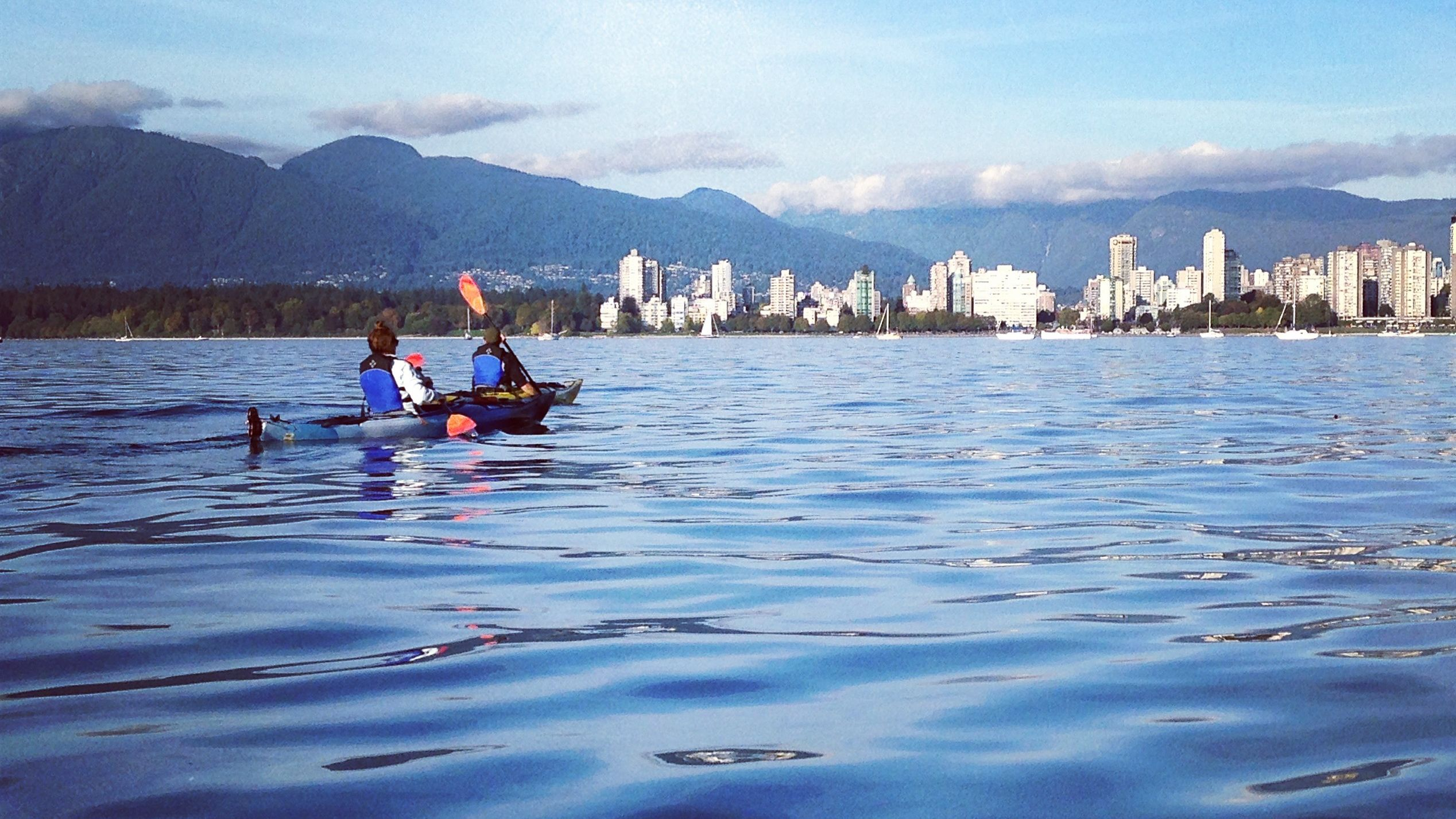 Kayakers paddling across river.