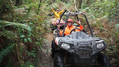 Buggy and ATV riders on a muddy path through the rainforest in New Zealand