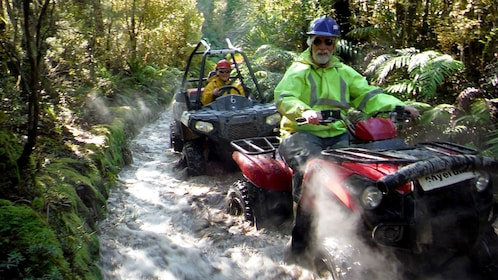 ATV and dune buggy splashing through a river in New Zealand