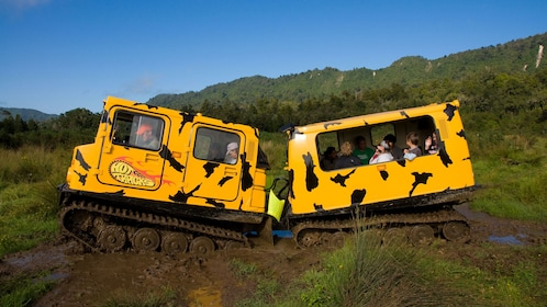 Hagglund vehicle with passengers driving through a muddy field in New Zealand