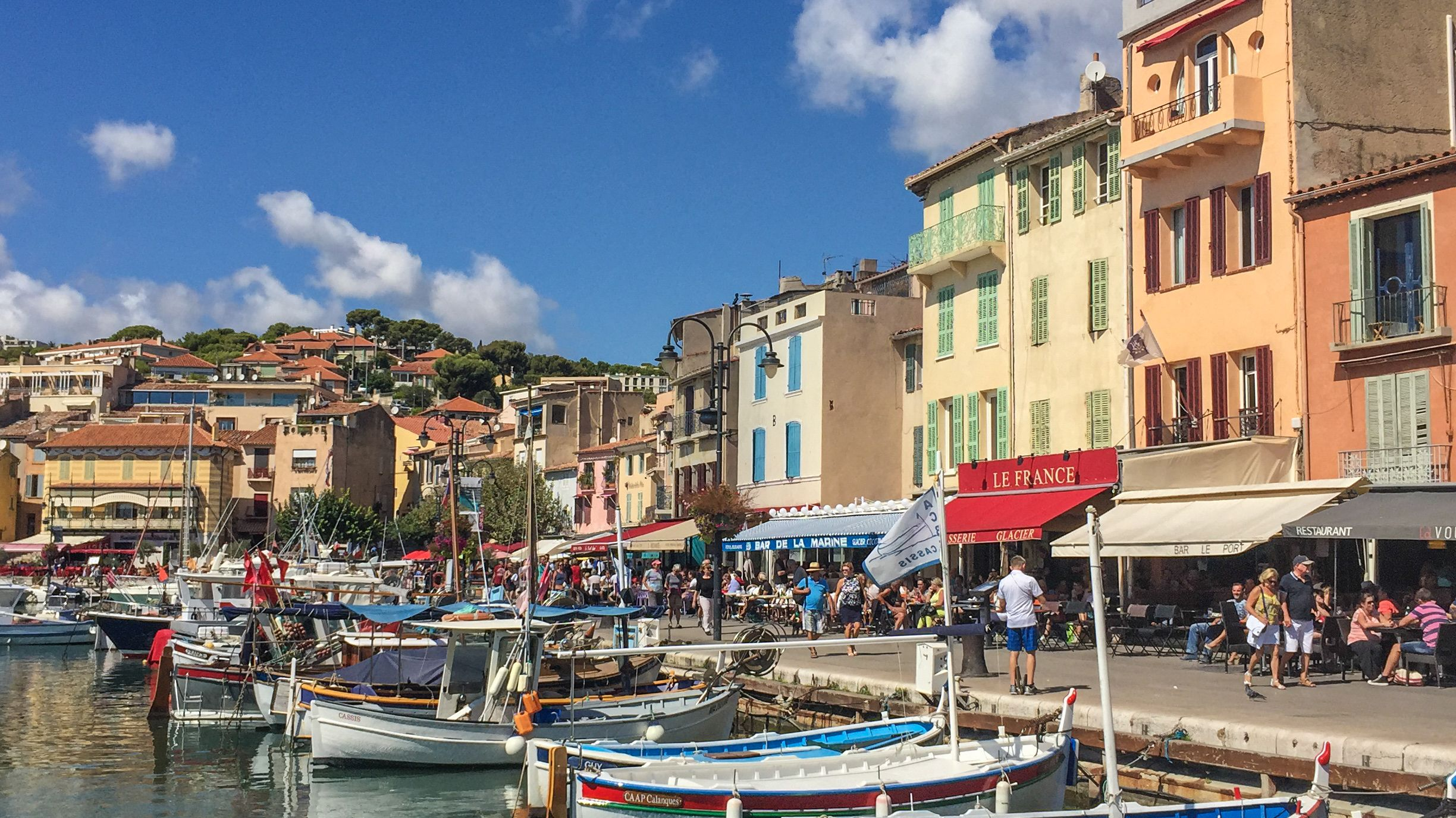 View of Cassis with several docked boats and shops in the distance.
