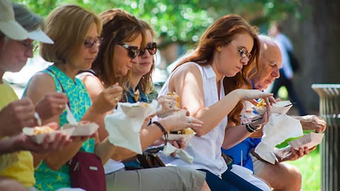 group eating lunch on a bench in Savannah