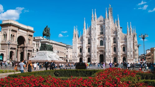 Exterior view of Duomo di Milano with rose garden seen in front.