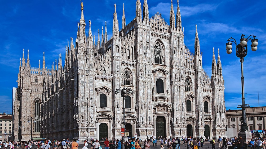 Show item 3 of 6. Angled exterior view of Milan Cathedral with hundreds of people walking about.