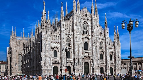 Angled exterior view of Milan Cathedral with hundreds of people walking about.