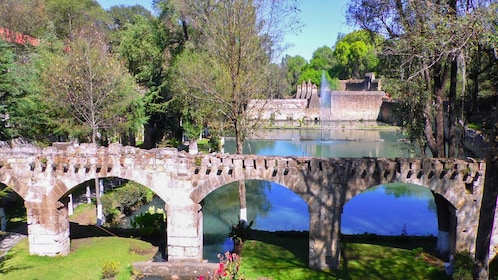 View of stone bridge surrounded by beautiful pond and garden.