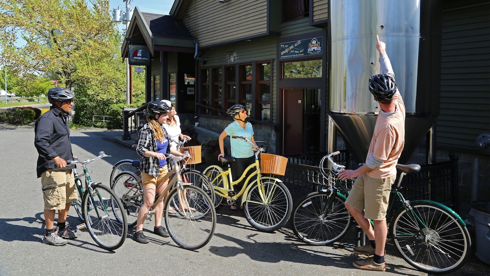 Show item 1 of 5. Bicycling group with tour guide outside a brewery in Victoria