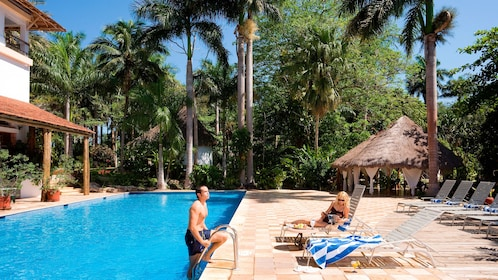 Man walks up swim ladder of a pool to a woman on a beach chair in a Mexican resort