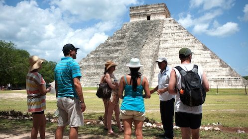 Private tour guide and group of people in front of a pyramid of Chichen Itza