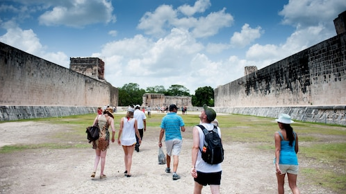 A group of people walk through the ruins of Chichen Itza