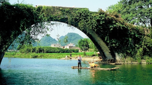 Man steering a bamboo raft under a bridge on the Li River in Guilin