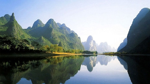 Tall green mountains line the bank of the Li River in Guilin
