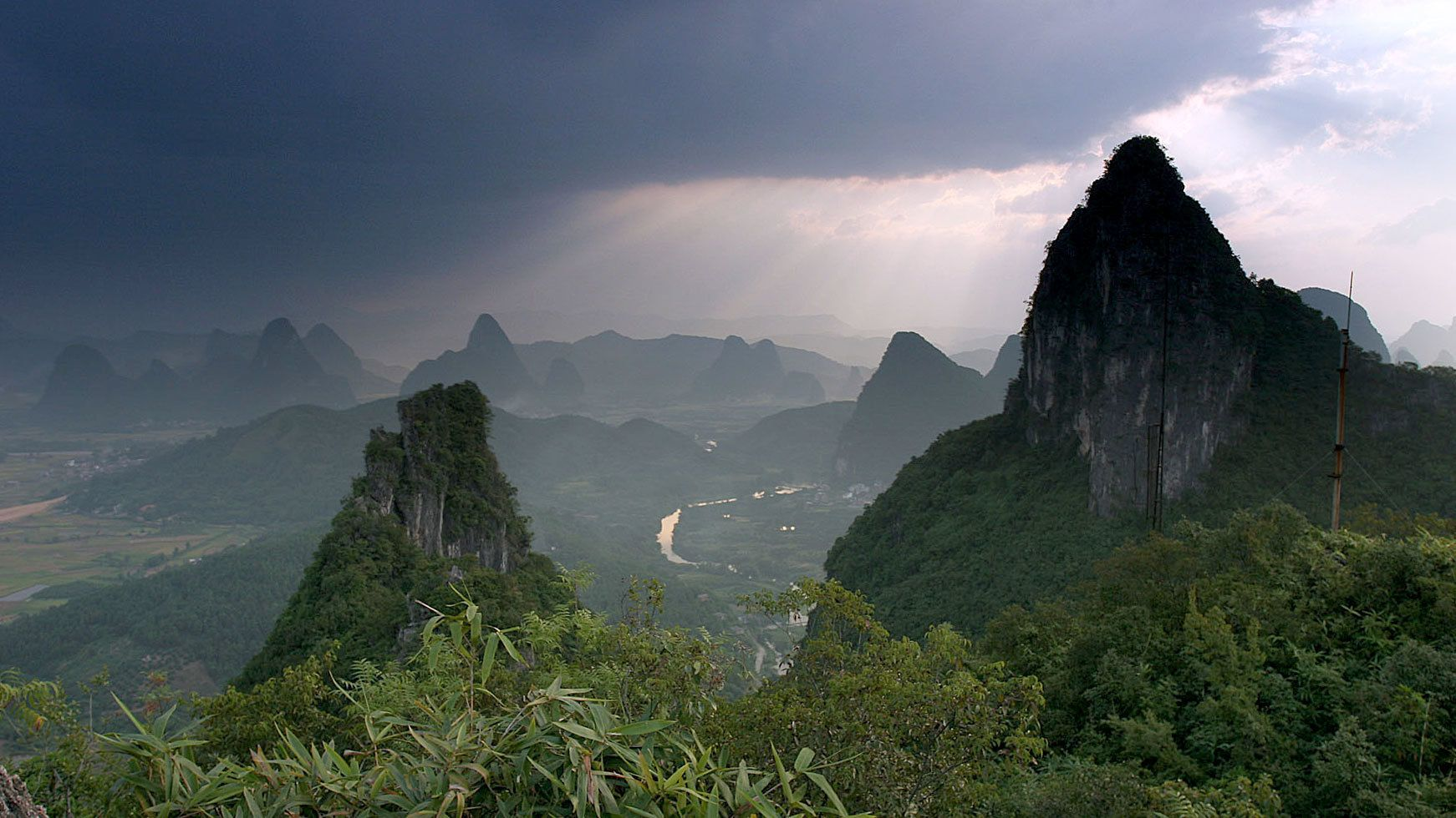 Sunlight streaming through the clouds on the mountains surrounding Yangshuo
