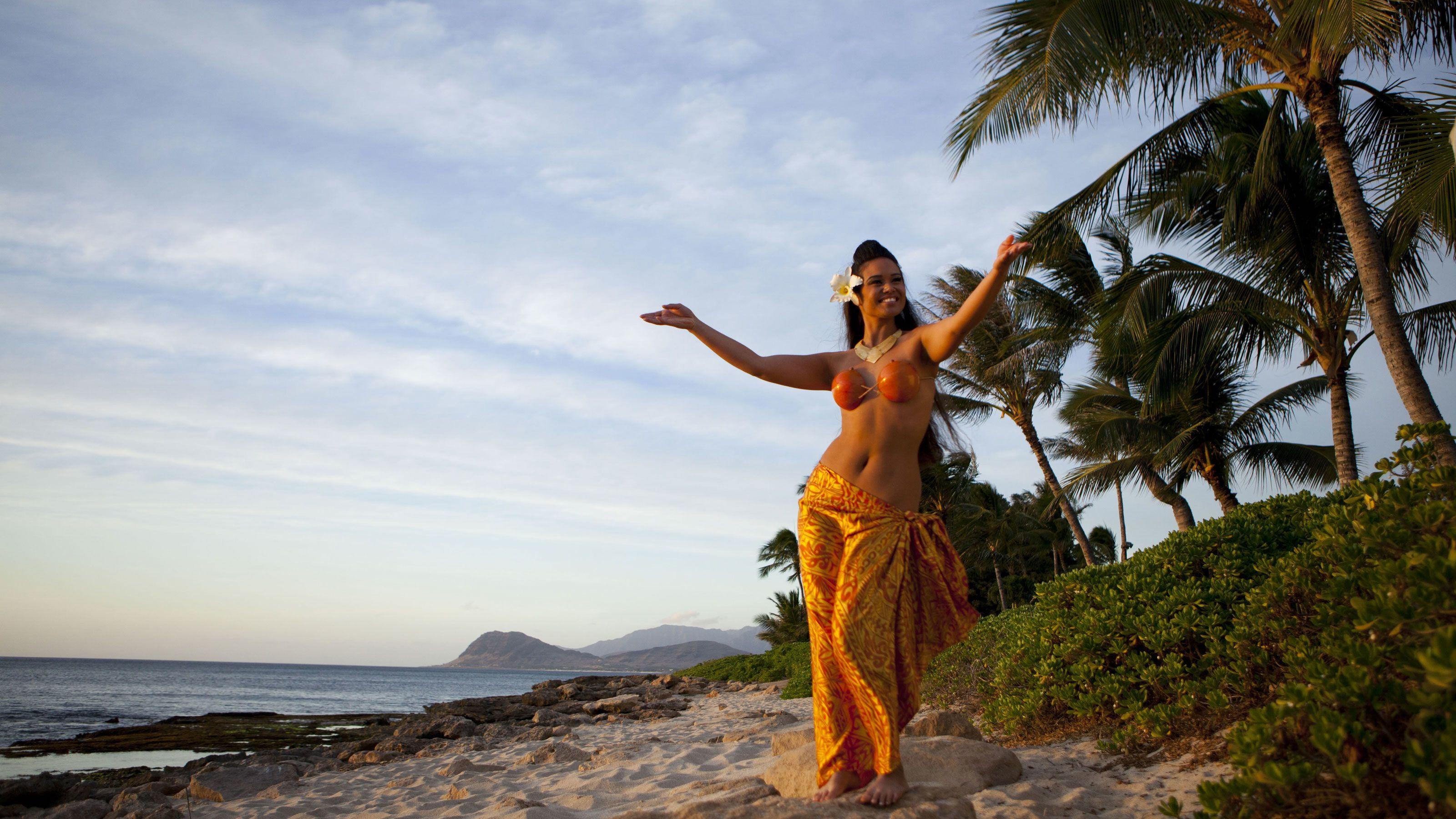 Lovely woman in orange dress on the beach in Oahu