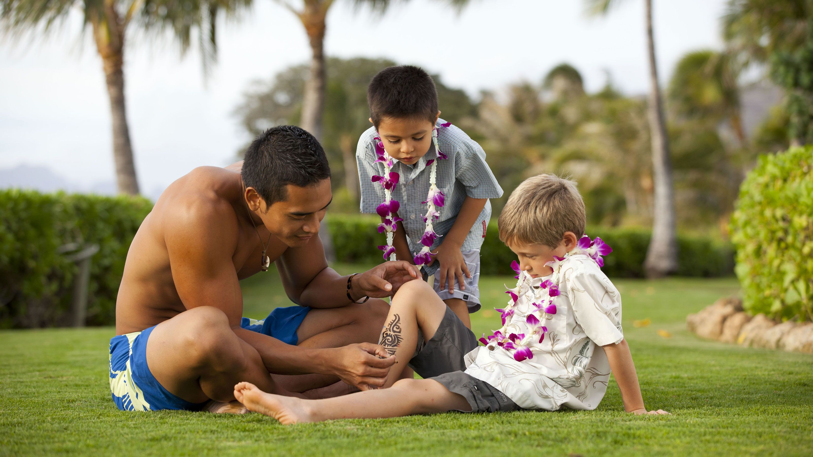 Man painting tribal art on young boy in Oahu