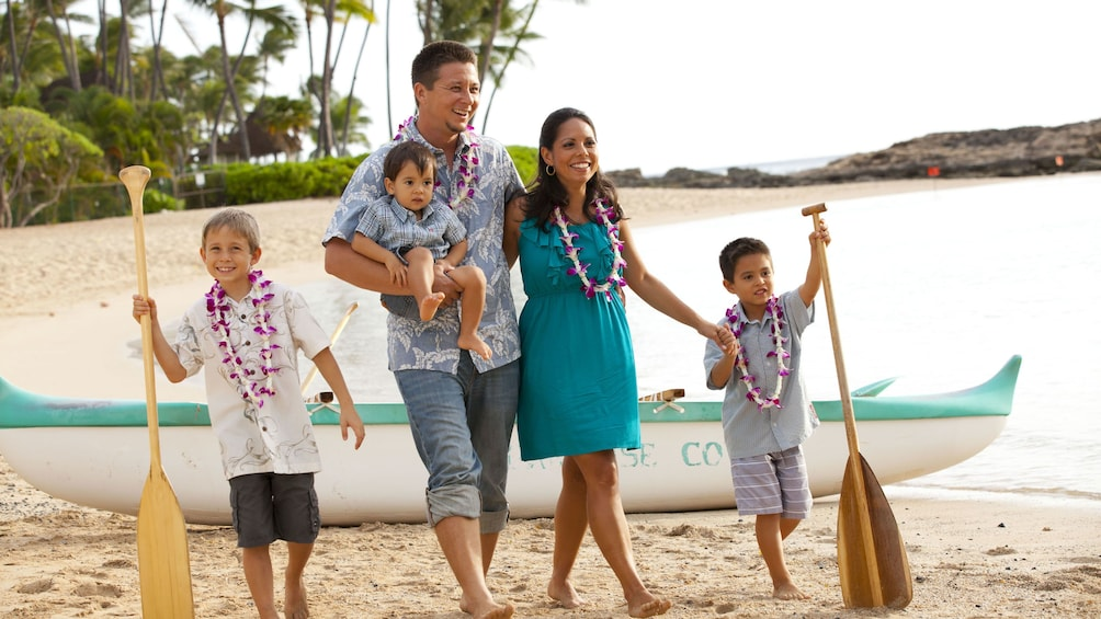 Family wearing leis on the beach in Oahu