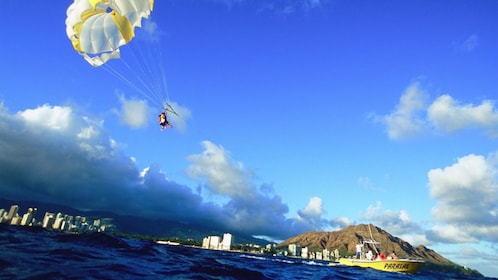 Friends on American flag parasail with view of island