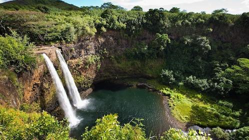 twin waterfalls flowing into pool in cove in Kauai