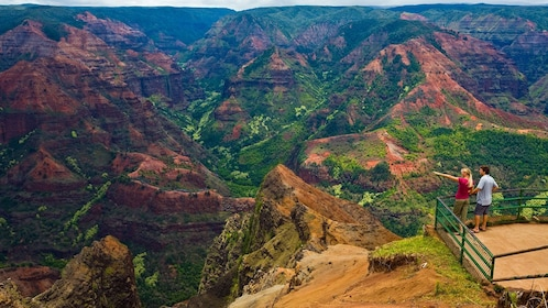 two people overlooking landscape of hills in Kauai