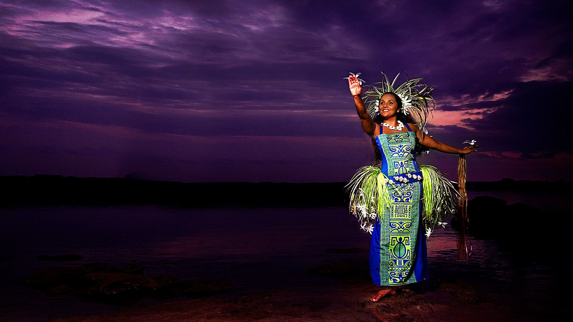 woman performer standin with bird on one hand and reaching out with the other in Haleo luau on the Big Island of Hawaii