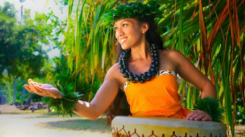 woman in luau costume playing drum with right hand out in Haleo luau on the Big Island of Hawaii