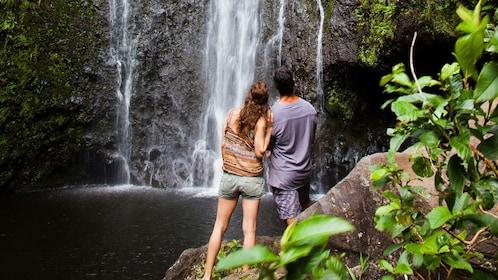 Couple enjoying view of waterfall in Oahu