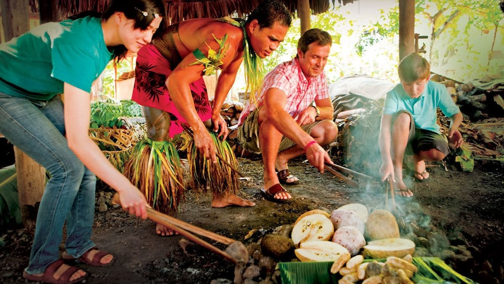 Participants moving stones around a fire