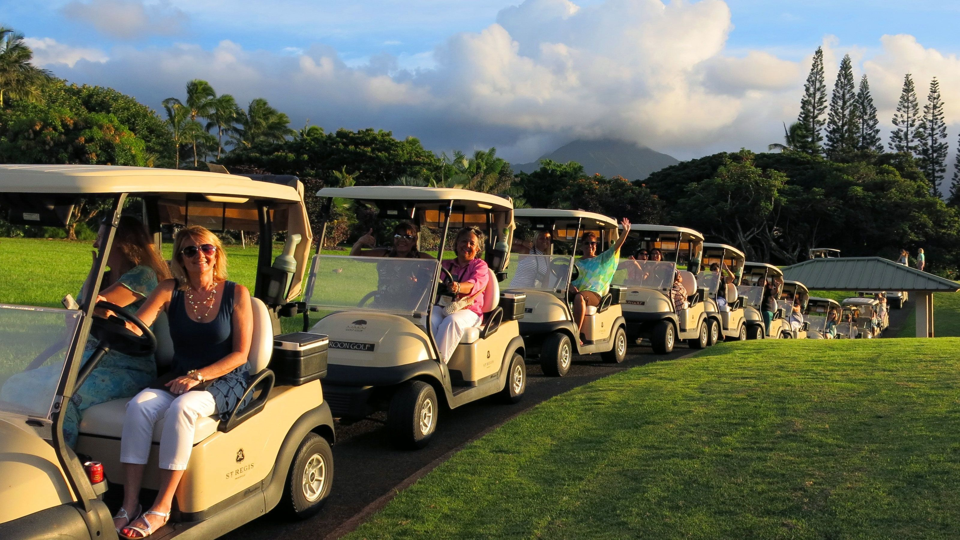 Row of tour group in golf carts on Kauai