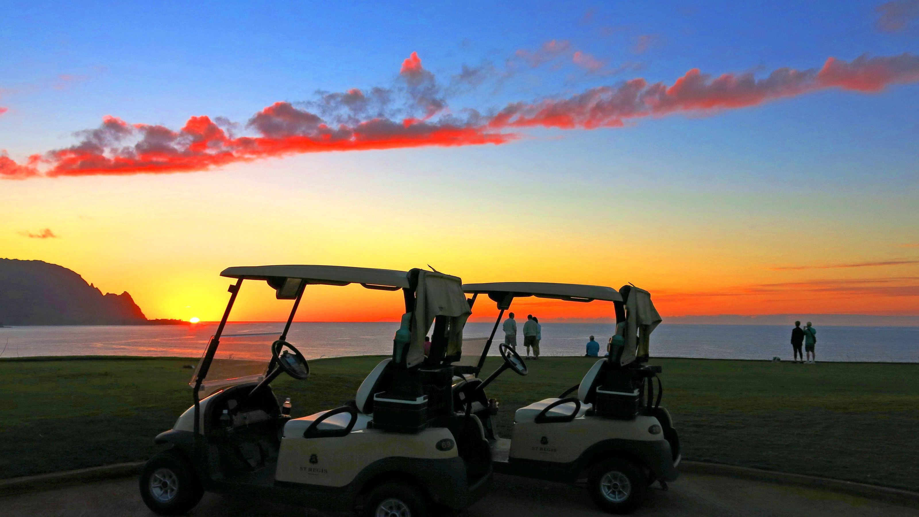 Golf carts on the course at sunset on Kauai