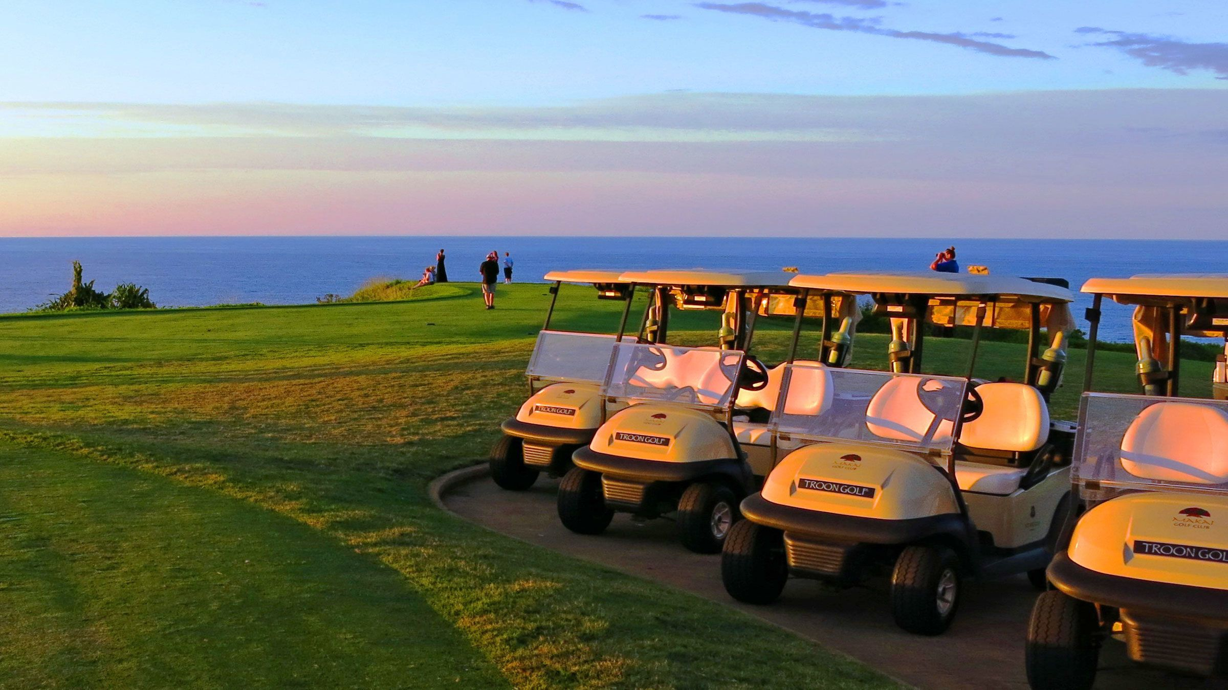 Parked golf carts at sunset on Kauai