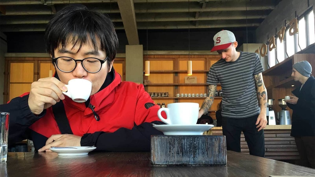 Man sipping coffee at the Pioneering Eastside Roasters Coffee Tour in Portland