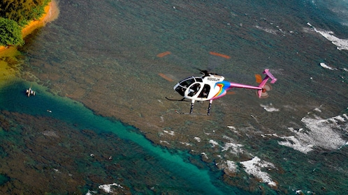 helicopter flying over ocean by island shore in Kauai