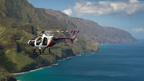 helicopter flying over ocean by island cliffs in Kauai
