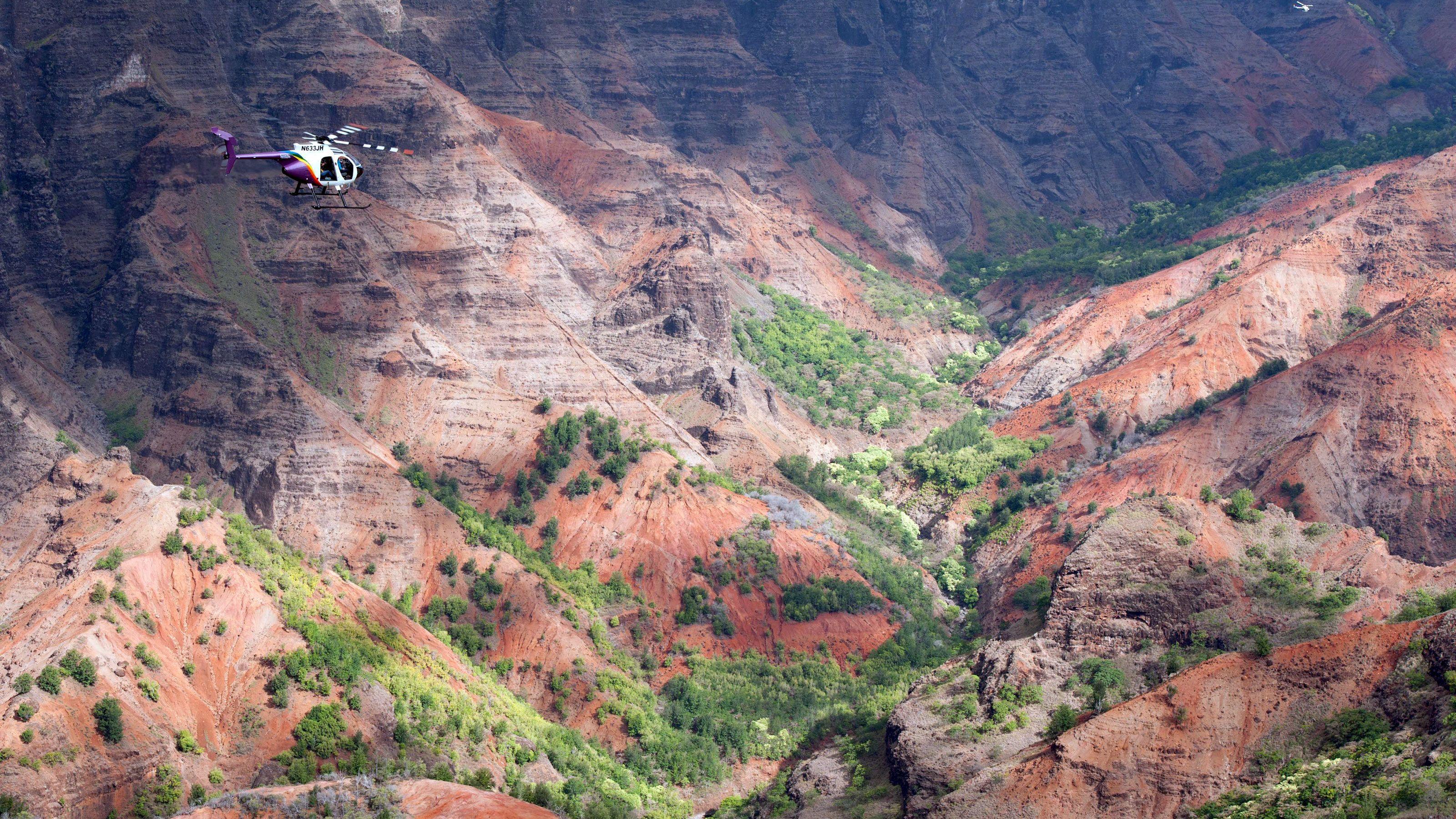 helicopter flying through mountain ridge in Kauai