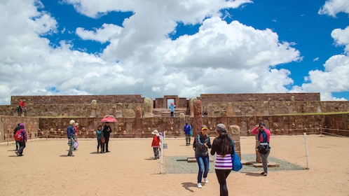 Several tourists walking about Tiwanaku ruins.