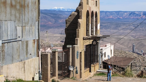 Man in front of the remains of a building facade in Jerome