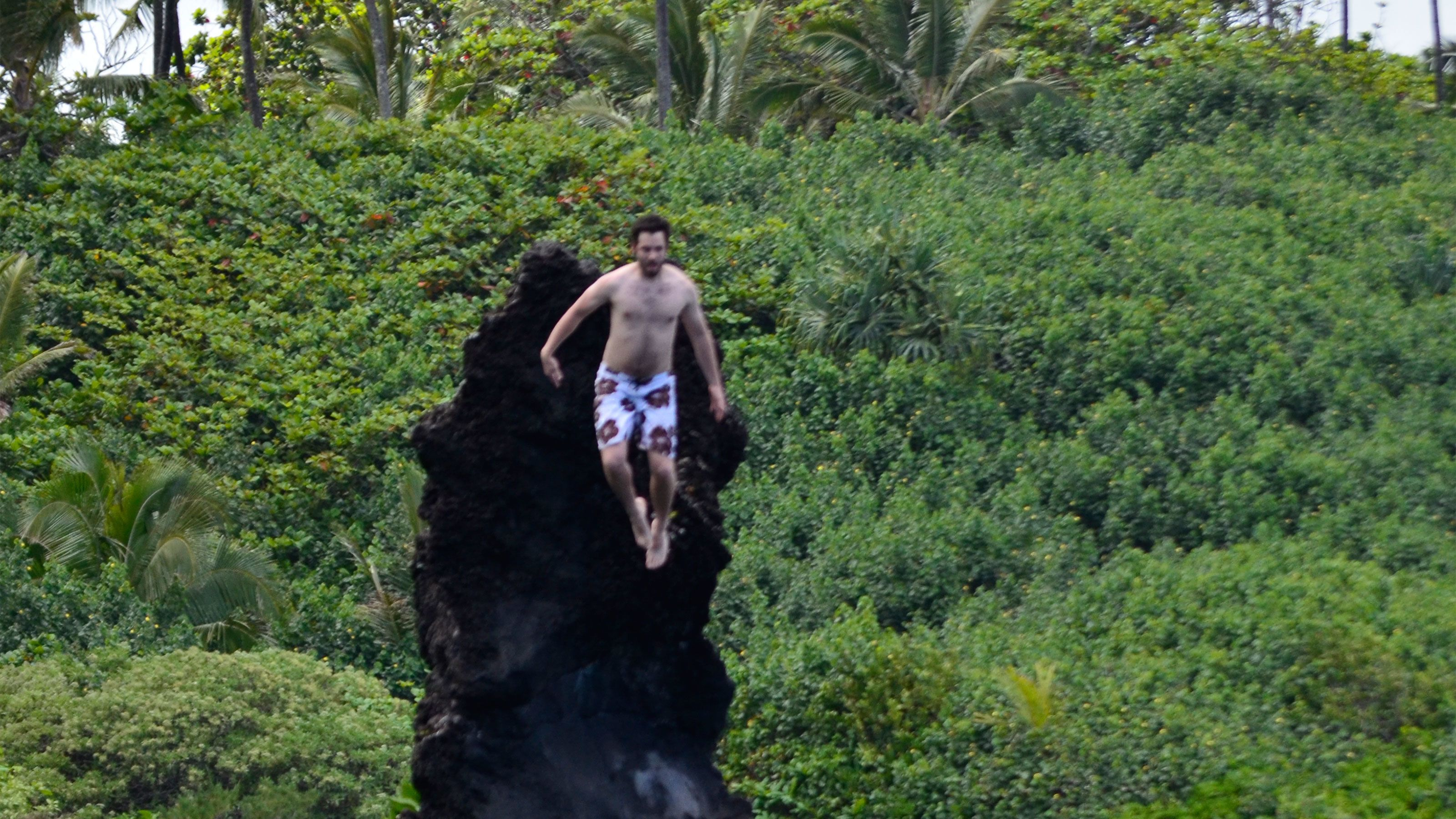 Man jumping into a waterfall in Hana