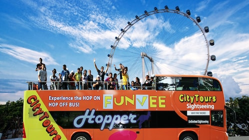 Hop on hop off bus with ferris wheel in the background in Singapore