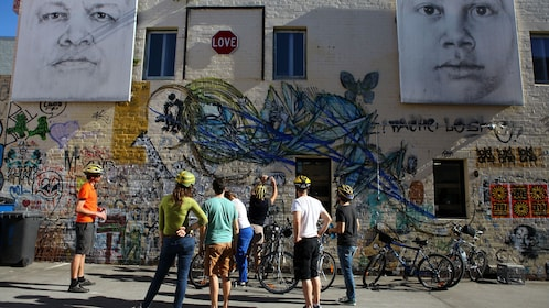 Bicycle tour group photographs street art in Brisbane