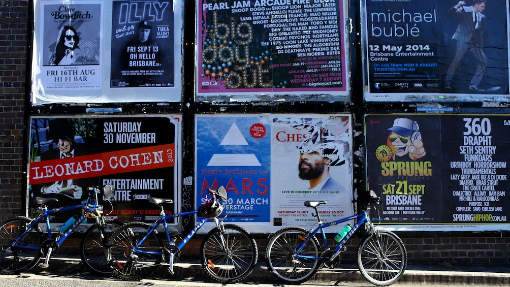 Bicycles parked by wall of posters in Brisbane