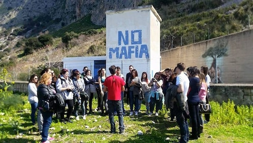 Group gathers around a building that says No Mafia on it.