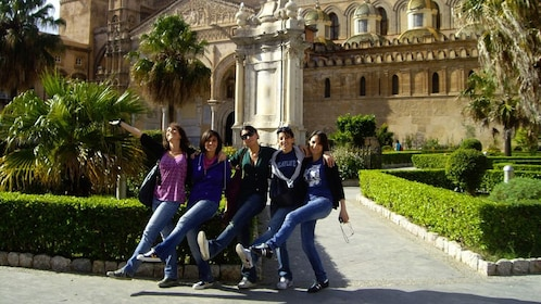 Four women hold their legs up in front of a fancy building in Palermo