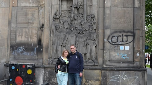 people standing in front of carved mural