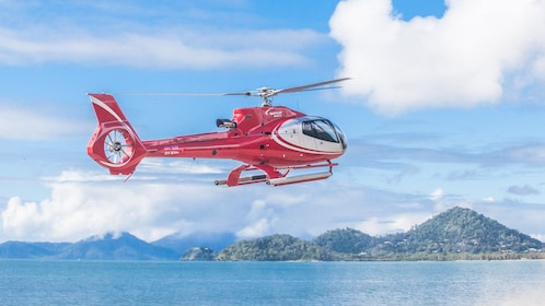 Red tour helicopter shown flying over ocean waters.