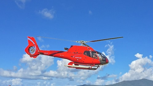 Red tour helicopter shown mid-flight.