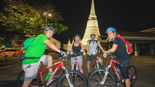 Several tourists posing together on bikes in parking lot.
