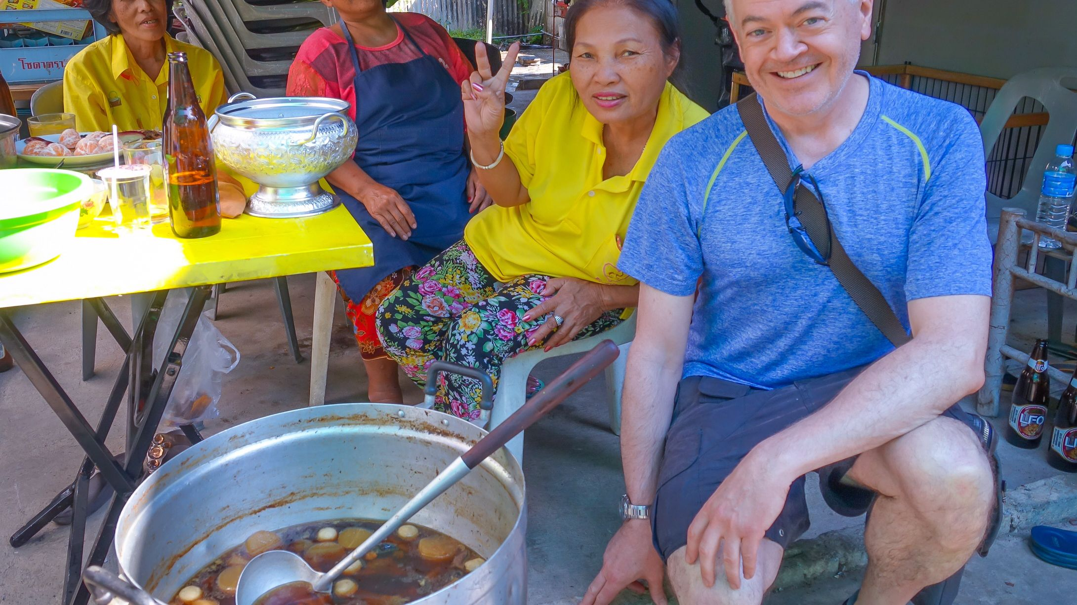 Male tourist and local women posing with large pot of freshly prepared soup.