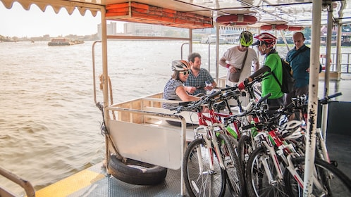 Cyclists riding on small boat with bikes.