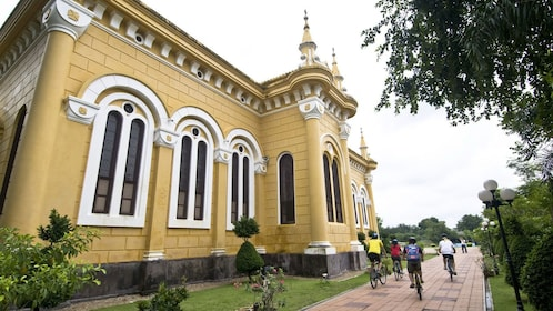 biking along a historic yellow building in Bangkok