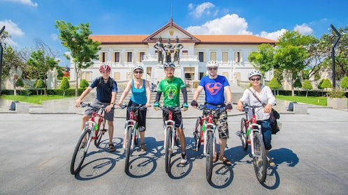 Cyclist posing in front of local museum on bicycles.